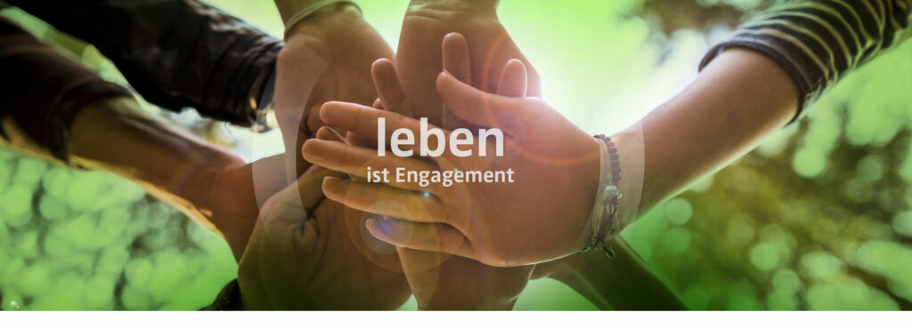 """Das Bild zeigt Hände, die als Gemeinschaftssymbol aufeinander liegen. In der Mitte steht: """"Leben ist Engagement""""."""